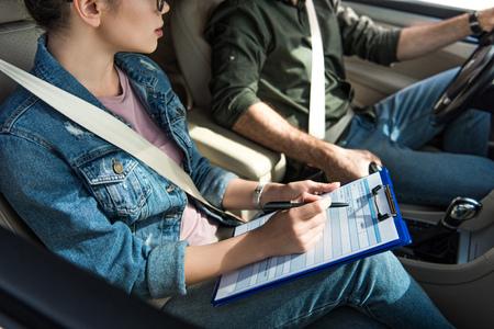bijgesneden afbeelding van student en leraar in auto op rijexamen