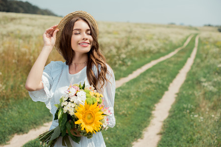 portrait of smiling woman in white dress with bouquet of wild flowers in field 스톡 콘텐츠 - 109614138