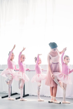 young woman teaching adorable kids dancing in ballet school