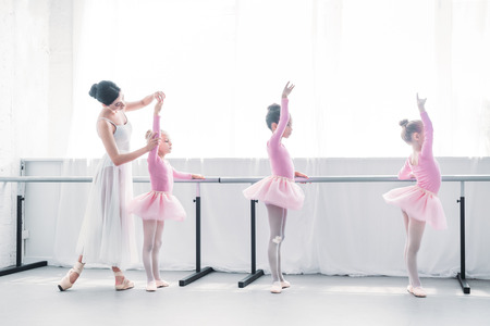 side view of ballet teacher exercising with children in ballet school