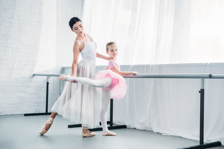 beautiful child in pink tutu practicing ballet with young teacher in ballet studio Zdjęcie Seryjne
