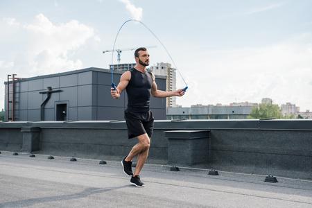 beau sportif formation avec corde à sauter sur le toit