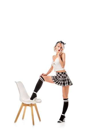seductive blond woman in short plaid skirt and knee socks standing with one leg on chair isolated on white