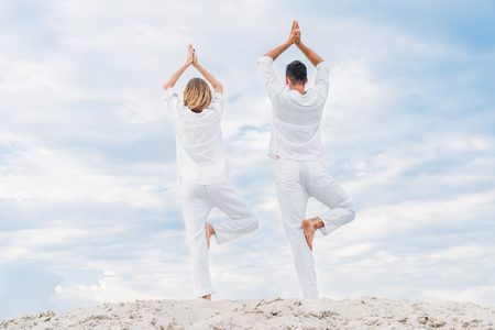 rear view of couple in white clothes practicing yoga in tree pose (Vrksasana) on sandy dune Reklamní fotografie - 109614612