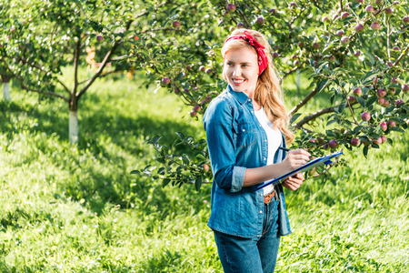 attractive farmer holding clipboard in apple garden at farm and looking away