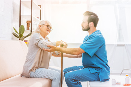 side view of male nurse supporting senior woman with walking cane Stock Photo