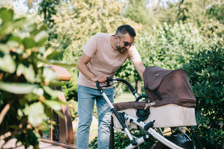 smiling father looking at baby carriage in park