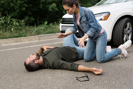 driver squatting above pedestrian after car accident on road Reklamní fotografie