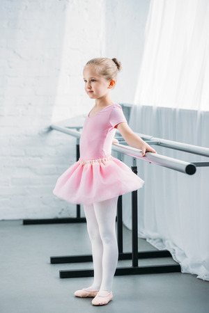 side view of kid in pink tutu practicing ballet and looking away in ballet studio Zdjęcie Seryjne