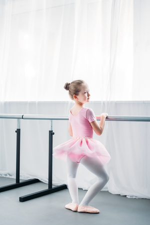 back view of adorable little ballerina exercising in ballet school