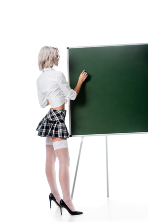 blond woman in seductive school uniform and stockings writing on empty chalkboard isolated on white