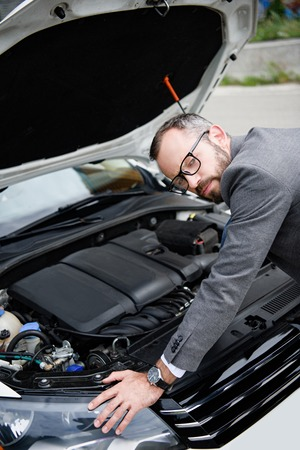 handsome businessman leaning on open car hood and looking at camera Фото со стока