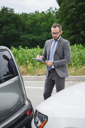 handsome businessman writing something to car insurance after car accident on road