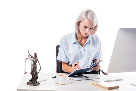 portrait of focused lawyer working at workplace with cup of coffee and notebooks isolated on white