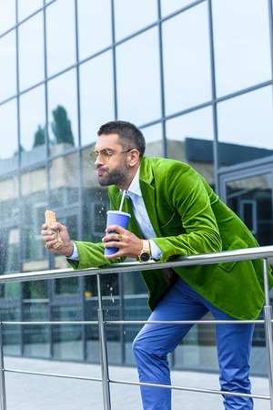 side view of man in green velvet jacket with french hot dog and soda drink in hands on street
