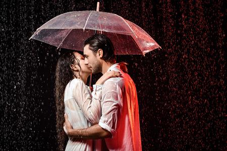 vista laterale della coppia romantica in camicie bianche con ombrello in piedi sotto la pioggia su sfondo nero