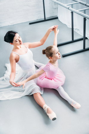 high angle view of adult ballerina exercising with cute little child in pink tutu in ballet school
