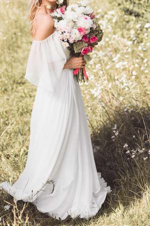 cropped shot of tender young bride in wedding dress holding beautiful bouquet of flowers outdoors