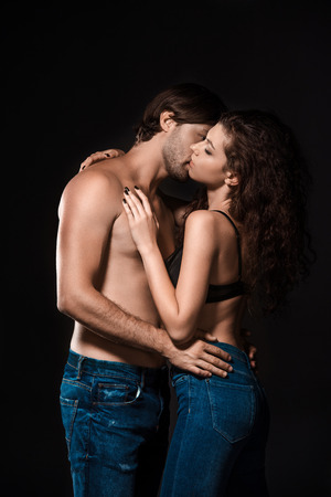 9f4ad13c67 side view of sexy shirtless couple kissing isolated on black Stock Photo