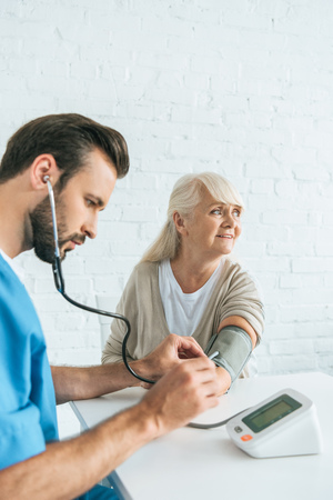 male nurse in stethoscope measuring blood pressure to smiling senior woman