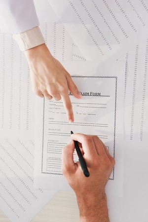 top view of man signing insurance claim form while doctor pointing at it
