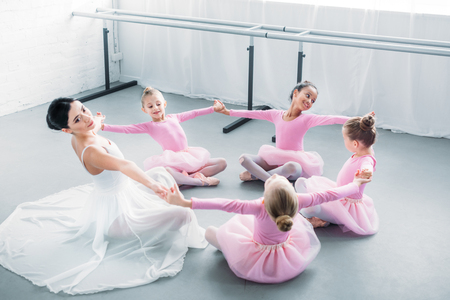 adorable little ballerinas and young teacher practicing together in ballet school Zdjęcie Seryjne