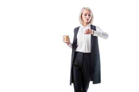 portrait of businesswoman in formal wear with coffee to go in hand checking time isolated on white Imagens