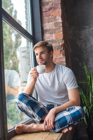 selective focus of young man sitting with cup of coffee on windowsill Фото со стока