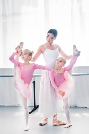 young ballet teacher exercising with small ballerinas in ballet school