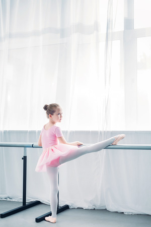 back view of little ballerina in pink tutu stretching in ballet school