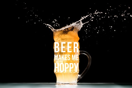 """mug of light beer with foam and splashes at table on black background with """"beer makes me hoppy"""" inspiration"""