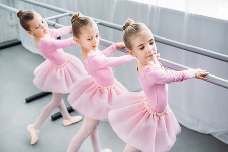 high angle view of elegant little ballerinas dancing in ballet school