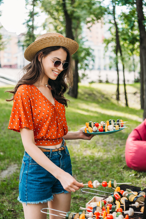 side view of smiling young woman in hat and sunglasses taking vegetables from grill in park