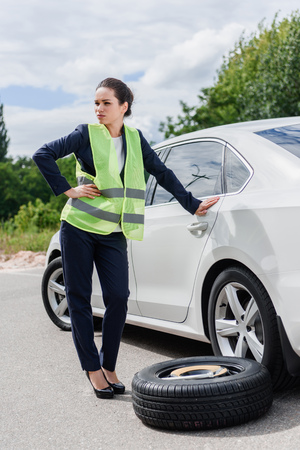 attractive businesswoman in light green vest standing on road near broken car Фото со стока