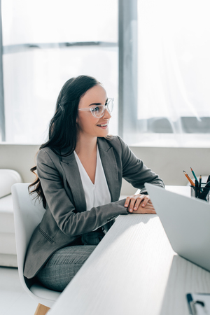 smiling businesswoman siting at table in office and looking away