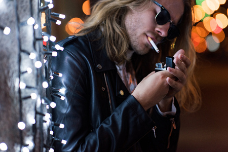 handsome young man in sunglasses and leather jacket smoking cigarette under garland on street at night