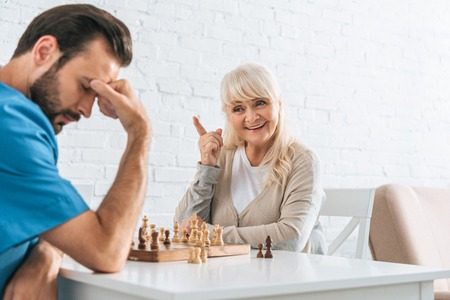 smiling senior woman pointing with finger and looking at upset man after chess game