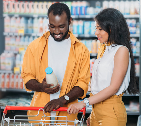 young african american couple with shopping trolley choosing milk in supermarket Stockfoto