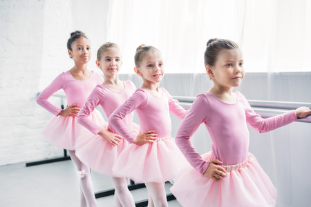 adorable little ballerinas practicing ballet in studio
