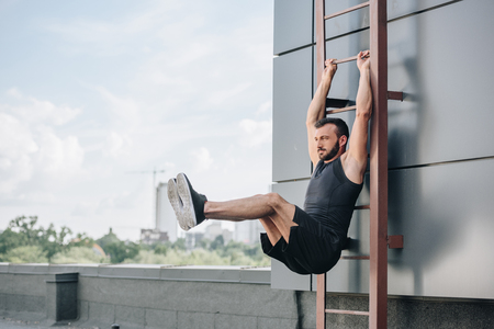 Handsome sportsman doing leg raises on ladder on roof Stock fotó