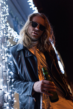 bottom view of handsome young man in sunglasses and leather jacket holding bottle of beer and standing under garland on street at night