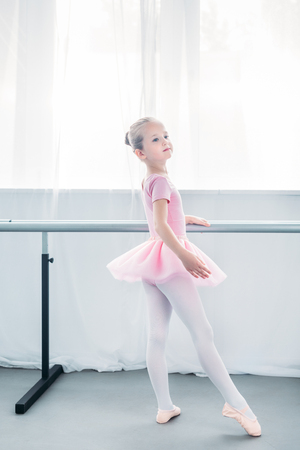 adorable little ballerina in pink tutu practicing ballet and looking away