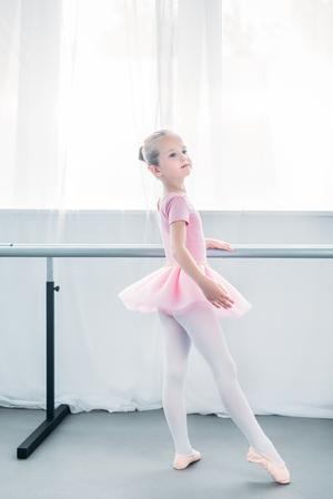 Adorable pequeña bailarina en tutú rosa practicando ballet y mirando a otro lado