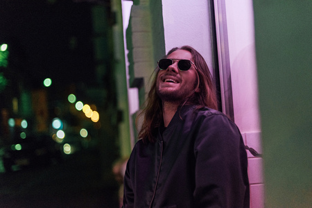 laughing young man in leather jacket and sunglasses on street at night under pink light