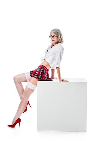Mujer rubia en seductora camisa blanca, falda de colegiala a cuadros y medias apoyándose en un cubo blanco aislado en blanco