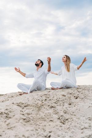 young fit couple on yogi meditating while sitting on sandy dune in lotus pose (padmasana)