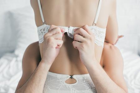 vue arrière partielle de l'homme enlevant le soutien-gorge de sa petite amie