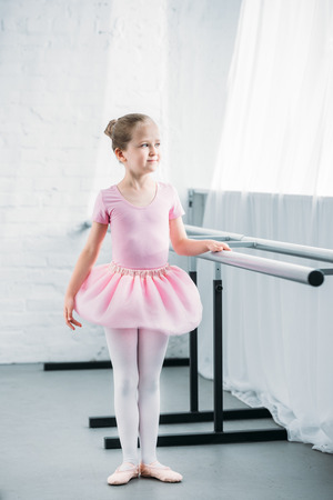 full length view of beautiful little ballerina in pink tutu looking away in ballet studio