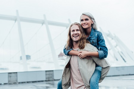 happy young woman piggybacking on boyfriends back and looking away