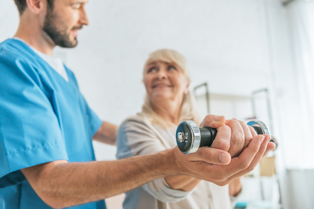 close-up view of social worker helping smiling senior woman exercising with dumbbells